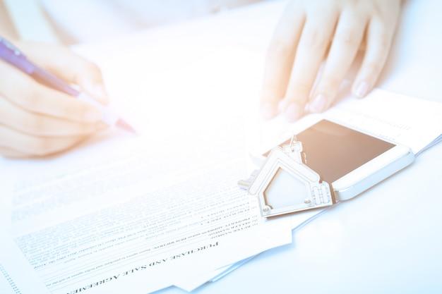 Vrouwenhand en huissleutel. ondertekend contract en sleutels van het pand met documenten. concept voor onroerend goed bedrijf.