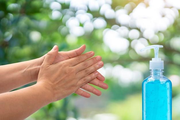 Vrouwenhand gebruiken alcoholge, handen wassen ter bescherming tegen besmettelijk virus, bacteriën, ziektekiemen en covid-19