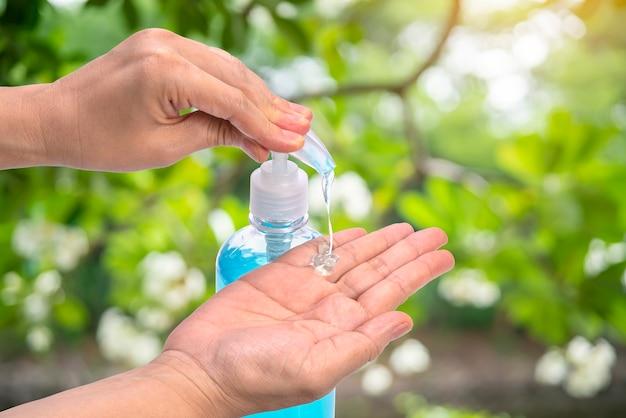 Vrouwenhand gebruiken alcoholgel, handen wassen ter bescherming tegen besmettelijke virussen, bacteriën, ziektekiemen en covid-19.