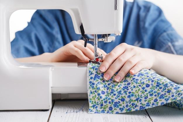 Vrouwenhand genaaide stof op naaimachine.