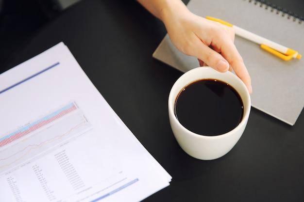 Vrouwenhand het drinken koffie met handelspapier