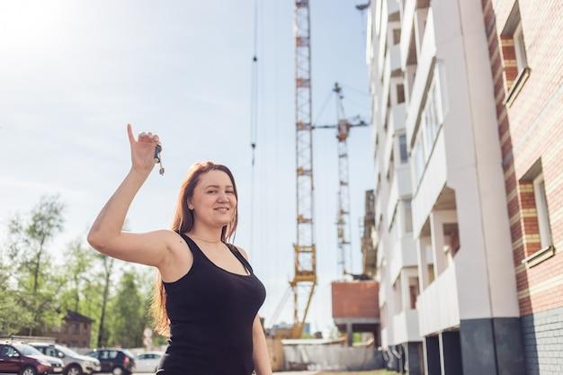 Vrouwenhand houdt de sleutels van een nieuw appartement vast