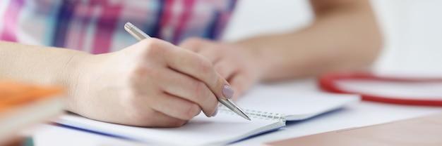 Vrouwenhand maakt aantekeningen met pen in notitieboekje