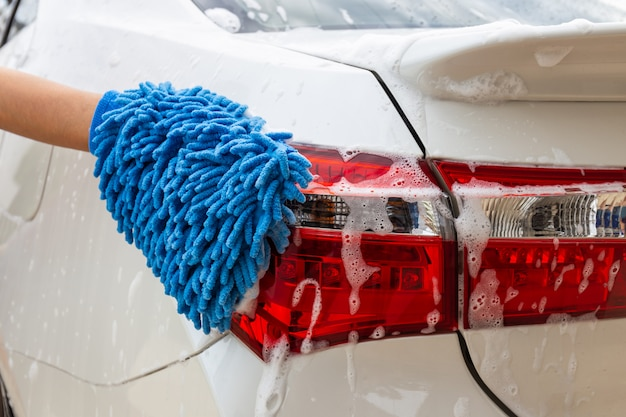 Vrouwenhand met blauwe microfiberstof die achterlicht moderne auto wassen of auto schoonmaken.