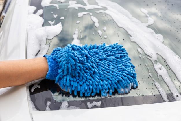 Vrouwenhand met blauwe microfiberstof die achteruitkijkspiegel moderne auto wassen of auto schoonmaken.