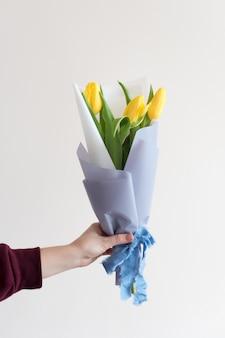 Vrouwenhand met de lentebloemen van de manicureholding.