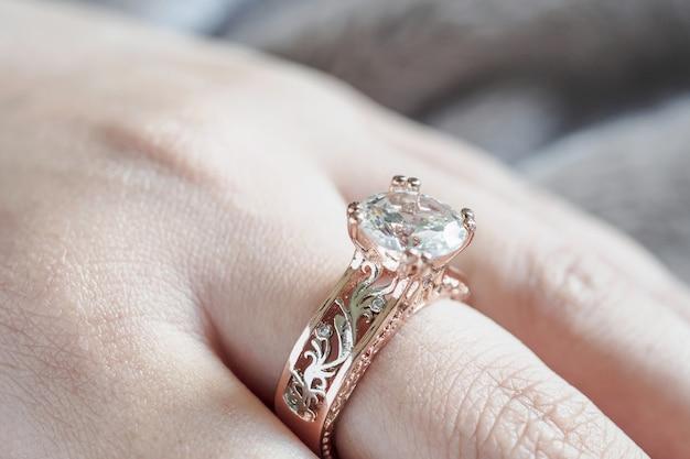 Vrouwenhand met de ring van de juwelendiamant op vinger