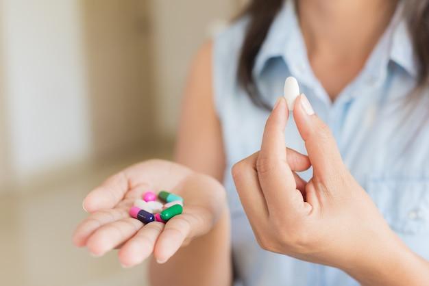 Vrouwenhand met de tabletten van de pillengeneeskunde in haar handen. gezondheidszorg concept