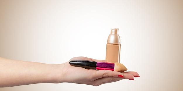 Vrouwenhand met een geïsoleerd stichtings kosmetisch hulpmiddel