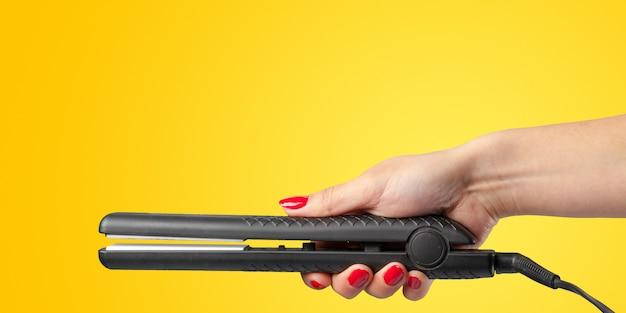 Vrouwenhand met een haarijzer op een kleur wordt geïsoleerd die