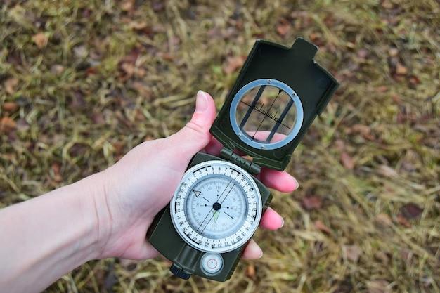 Vrouwenhand met een kompas op een achtergrond van lentegras close-up
