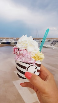 Vrouwenhand met een kopje met roze en geel ijs met slagroom