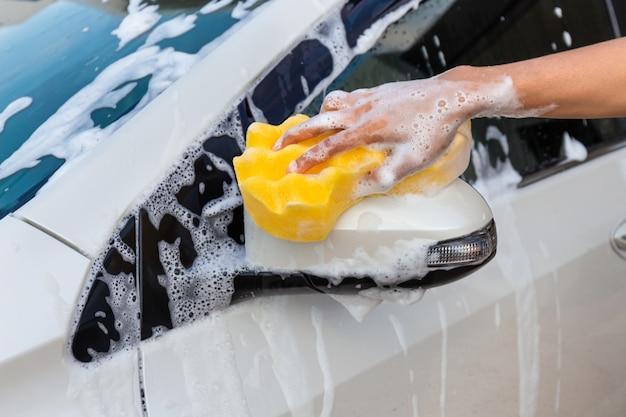 Vrouwenhand met gele spons die zijspiegel moderne auto wassen of auto schoonmaken.
