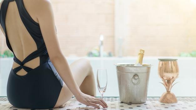 Vrouwenhand met glas wijn, dichtbij het bellenpool