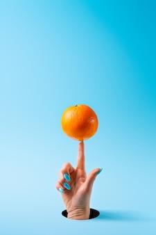 Vrouwenhand met lange geschilderde spijkers die oranje fruit op wijsvinger in evenwicht brengen door een gat dat in blauw document wordt gesneden