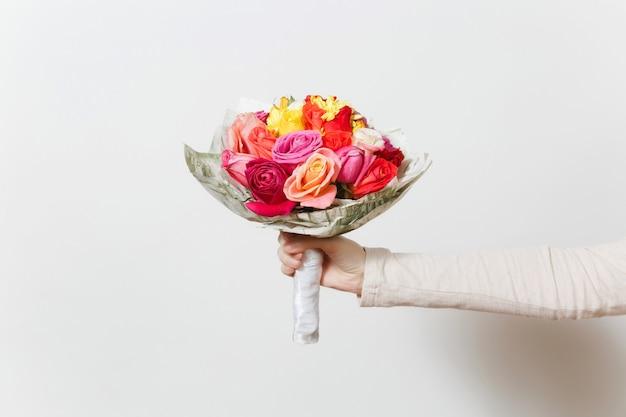 Vrouwenhand met mooi boeket van kleurrijke rozen, verschillende rode, gele, oranje bloemen. geïsoleerd op een witte achtergrond. st. valentijnsdag of internationale vrouwendag, vakantieconcept.