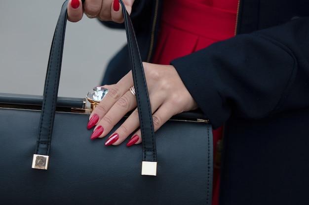 Vrouwenhand met mooie rode manicure die zwarte leerhandtas houdt
