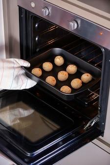 Vrouwenhand met pot die metalen bakplaat met kaasbrood uit de oven vangen. kaasbroodjes.