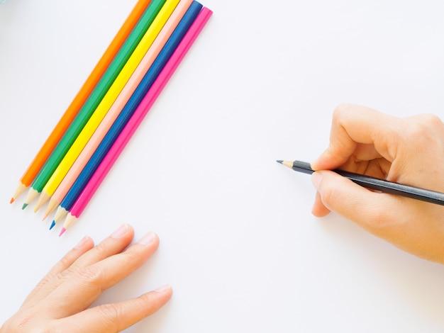 Vrouwenhand met potlood die op witboek schrijven.