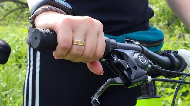 Vrouwenhand met ring op het stuur van een mountainbike