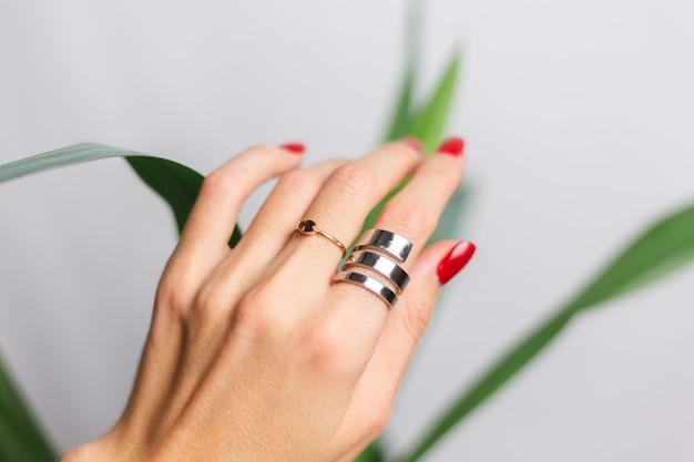 Vrouwenhand met rode manicure en twee ringen op vingers, op mooi groen tropisch palmblad. grijze muur erachter.