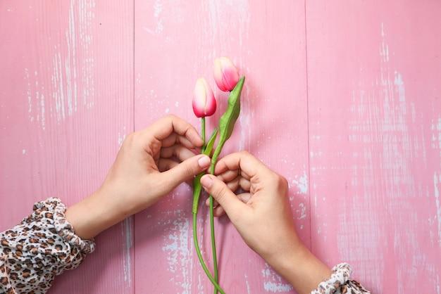 Vrouwenhand met tulpenbloem op roze ruimte