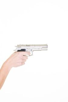 Vrouwenhand met zilveren kanon die bereid worden te schieten geïsoleerd op wit
