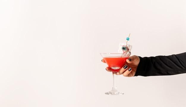 Vrouwenhand met zwarte spijkers die glas met enge rode halloween-cocktail op witte achtergrond houden