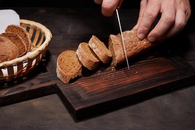 Vrouwenhand of chef-kok gesneden met een mes, een brood van wit brood, brood of stokbrood in plakjes, op een houten keuken board. concept van het koken van biologische natuurlijke boerderij voedsel of ontbijt, huiswerk.