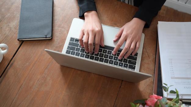 Vrouwenhand op toetsenbord van laptop terwijl het werken in huisbureau