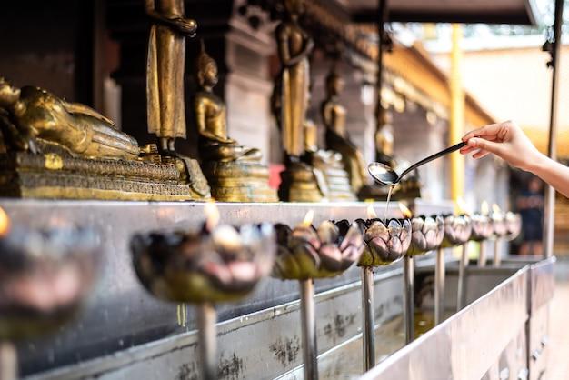Vrouwenhand opnieuw vullen oud in thaise de kaarskop van het stijlmetaal in de tempel van doi suthep, chiang mai, thailand