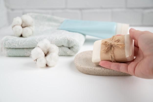 Vrouwenhand pakt nieuw stuk zeep uit dienblad in de badkamer