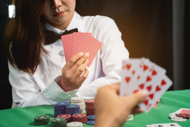 Vrouwenhandelaar of croupier schudt pokerkaarten in een casino op de achtergrond van een tafel, pokerspelconcept