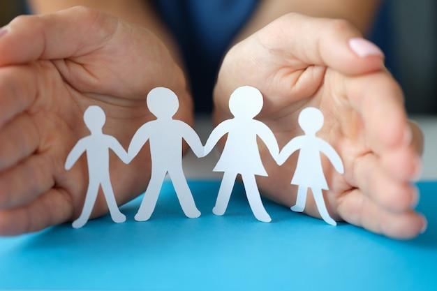 Vrouwenhanden beschermen een gezin met kinderen tegen het papieren welzijn en het comfort van moderne gezinnen
