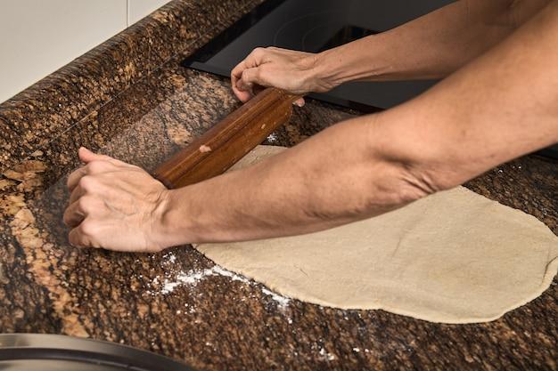Vrouwenhanden die aan een pizzadeeg werken