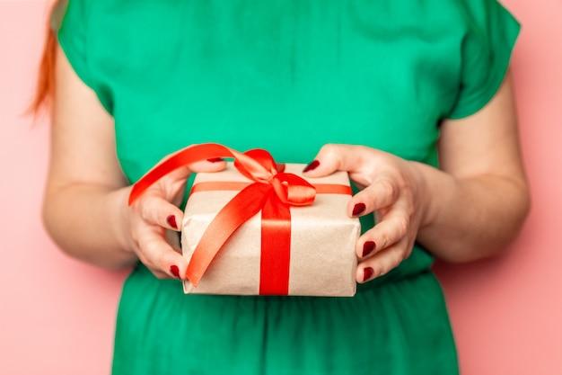 Vrouwenhanden die ambachtdocument giftdoos houden met als cadeau