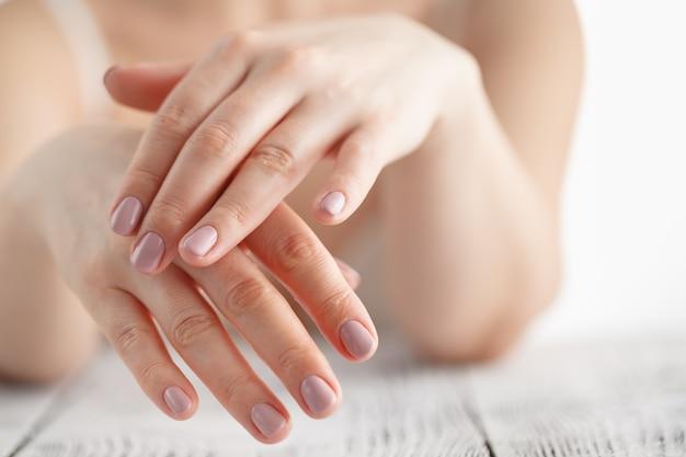 Vrouwenhanden die bevochtigende room toepassen op haar huid