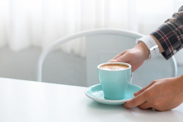 Vrouwenhanden die blauwe koffiekoppen in koffie houden dichtbij het venster.