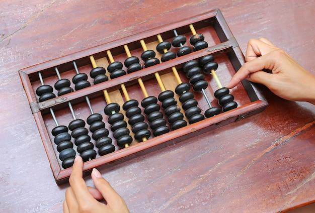 Vrouwenhanden die chinese abacus gebruiken