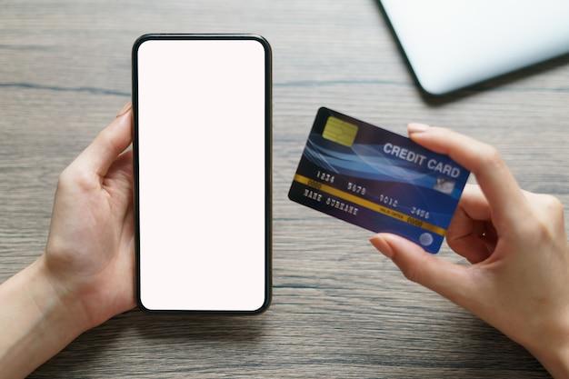 Vrouwenhanden die creditcard en het smartphone lege scherm houden
