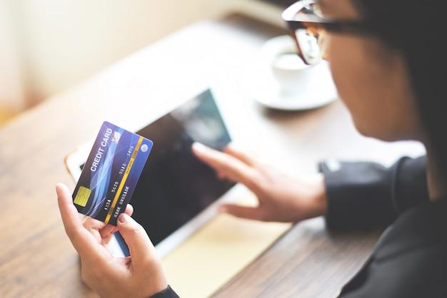 Vrouwenhanden die creditcard houden en tablet online het winkelen de portefeuille online betaling van het technologiegeld gebruiken