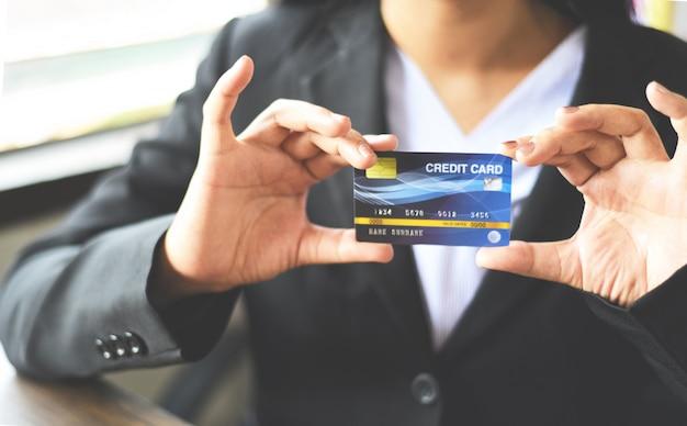 Vrouwenhanden die creditcard voor online het winkelen in een bureau houden