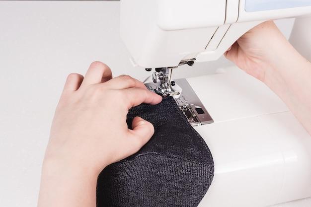 Vrouwenhanden die de naaimachine gebruiken om het gezichtsmasker te naaien tijdens de coronavirus-pandemie. zelfgemaakt zelfgemaakt beschermend masker tegen virus. preventieve uitrusting in quarantaine voor coronavirus