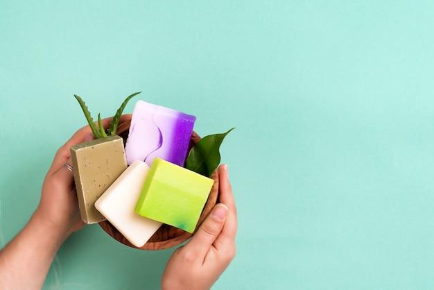 Vrouwenhanden die de natuurlijke organische staaf van de kleurenzeep op blauw houden. geen afval thuisconcept.