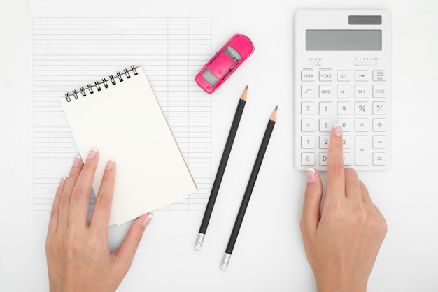 Vrouwenhanden die de uitgavenkosten van autokosten met document nota's, potlood, calculator, betalingenlijst en dollargeld berekenen