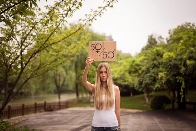 Vrouwenhanden die een aanplakbiljet met mannelijk en vrouwelijk symbool houden