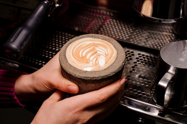 Vrouwenhanden die een concrete pot met latte houden