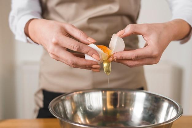 Vrouwenhanden die een ei breken om eiwit en dooiers te scheiden