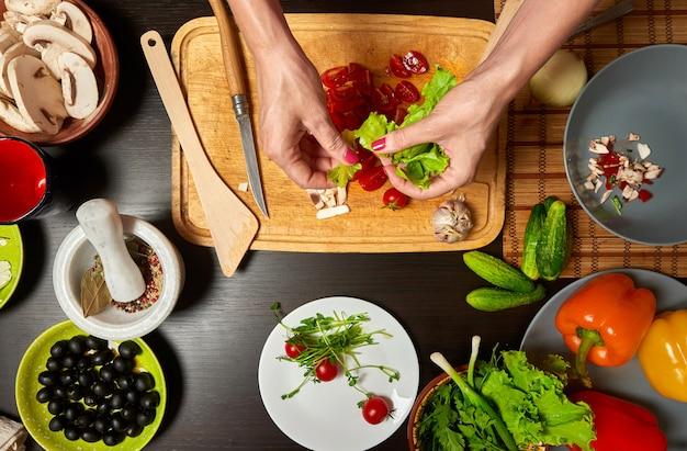 Vrouwenhanden die een gezonde salade voorbereiden