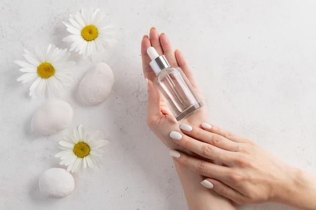 Vrouwenhanden die een glasfles met kosmetisch serum houden